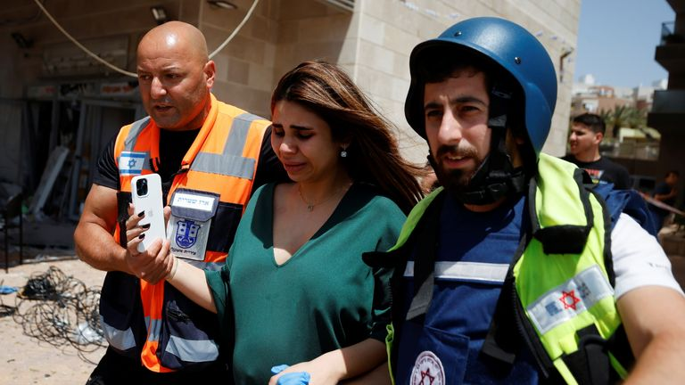 Israeli security personnel help a woman after a rocket attack on a shopping complex in Ashkelon