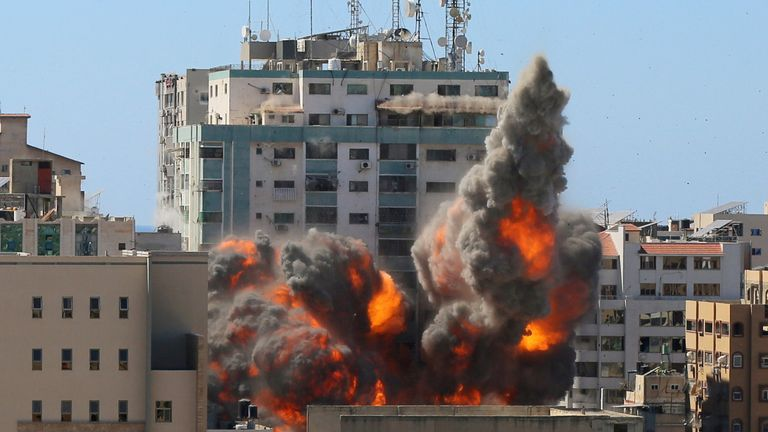 An explosion is seen near a tower housing AP, Al Jazeera offices (C) during Israeli missile strikes in Gaza city, May 15, 2021. REUTERS/Ashraf Abu Amrah NO RESALES. NO ARCHIVES.