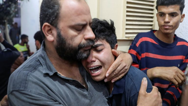 A man in Gaza is comforted after one of his relatives died in the violence