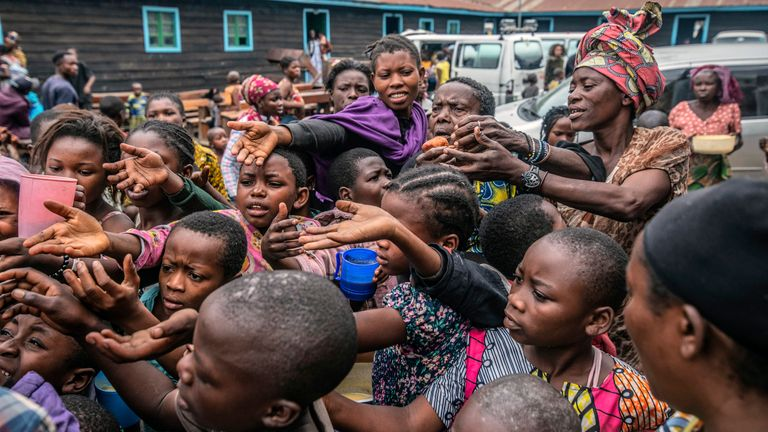 People who fled Goma, Congo gather at a food distribution point Friday, May 28, 2021  in Sake, some 25 kms (16 miles) west of Goma  where they found shelter following an official evacuation order five days after Mount Nyiragongo erupted. (AP Photo/Moses Sawasawa)