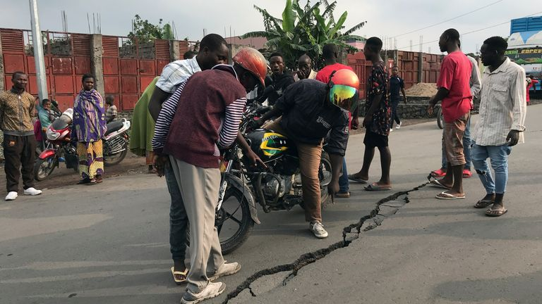 People inspect a crack on the road caused by earth tremors