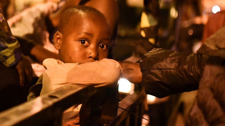 A child looks on as people gather with their belongings following a volcanic activities at Mount Nyiragongo near Goma, in the Democratic Republic of Congo May 22, 2021. REUTERS/Olivia Acland
