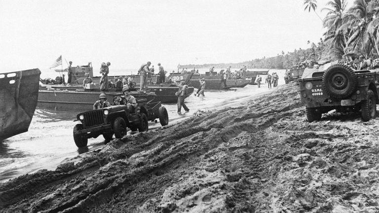 تفنگداران آمریکایی با رسیدن به ساحل با یک مخزن دوزیست سوار می شوند و در ساحل جزیره گوادالکانال در سلیمانز شروع به غرش می کنند ، 30 اوت 1942 (AP Photo / استخر Acme Wartime War / Sherman Montrose)
