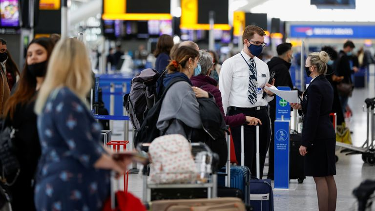 Passengers queue for check-in desks in the departures area of Terminal 5 at Heathrow Airport in London