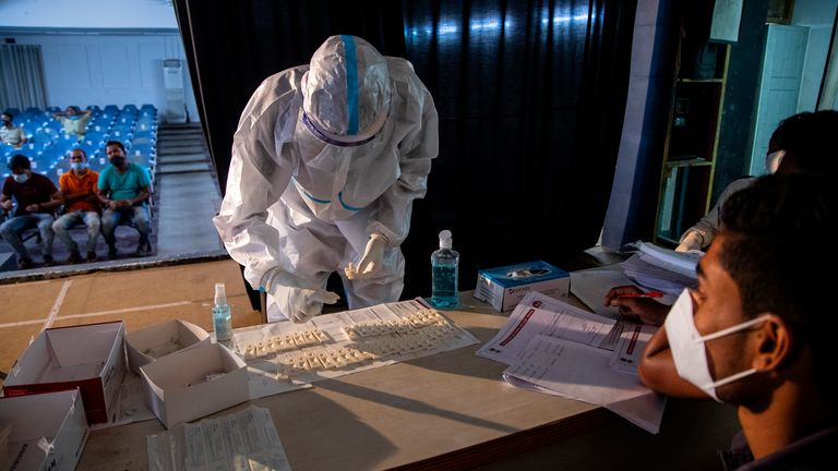 A health worker in PPE performs rapid test for COVID-19. Pic: AP