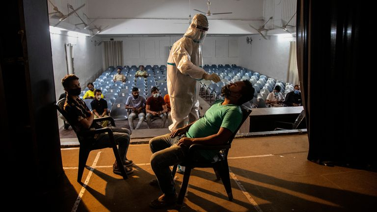 A health worker takes a nasal swab sample of an election official to test for COVID-19. Pic: AP