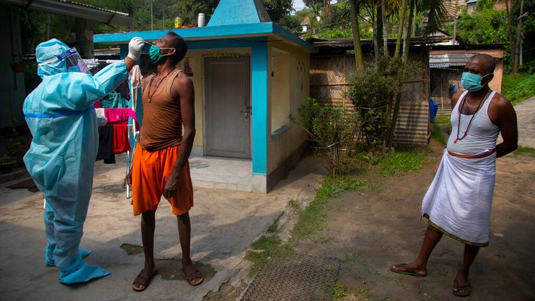 A heath worker takes a nasal swab sample to test in Gauhati, India. Pic: AP