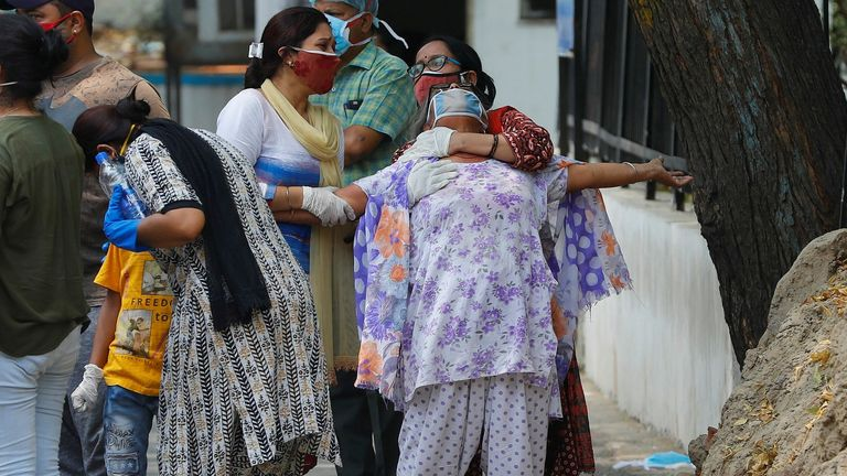 A woman mourns after seeing the body of her son who died after catching COVID-19 in New Delhi, India