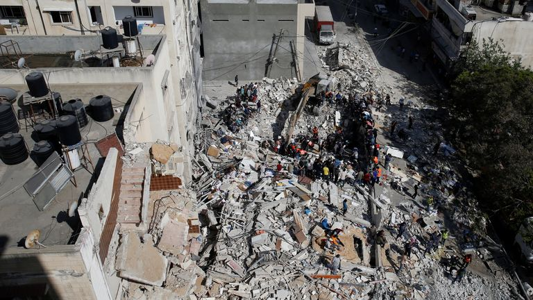 Rescue workers search for victims amid rubble at the site of Israeli airstrikes, in Gaza City