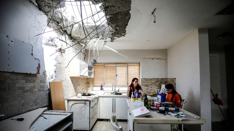 A family in Ashkelon sit in the kitchen of their house damaged by a rocket from Gaza