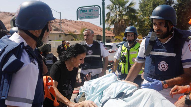 Medics evacuate a person injured after a rocket attack on Ashkelon, southern Israel