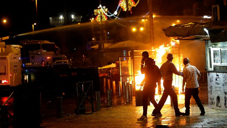An Israeli police water cannon is deployed near the Damascus Gate to the Old City of Jerusalem as a fire burns during clashes between police and Palestinian protesters. Pic: AP