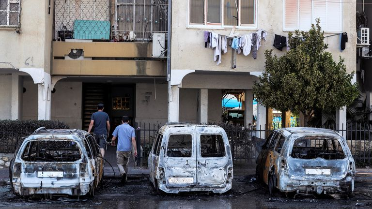 People walk next to burnt vehicles as they enter a building after violent confrontations in the city of Lod, Israel between Israeli Arab demonstrators and police, amid high tensions over hostilities between Israel and Gaza militants and tensions in Jerusalem May 12, 2021