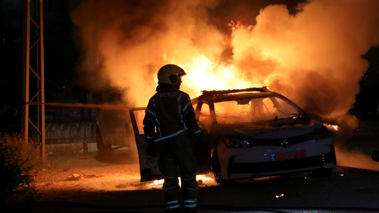An Israeli firefighter stands near a burning Israeli police car during clashes between Israeli police and members of the country's Arab minority in the Arab-Jewish town of Lod, Israel May 12, 2021.