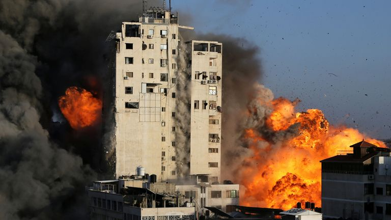 Smoke and flames rise from a tower building as it is destroyed by Israeli air strikes