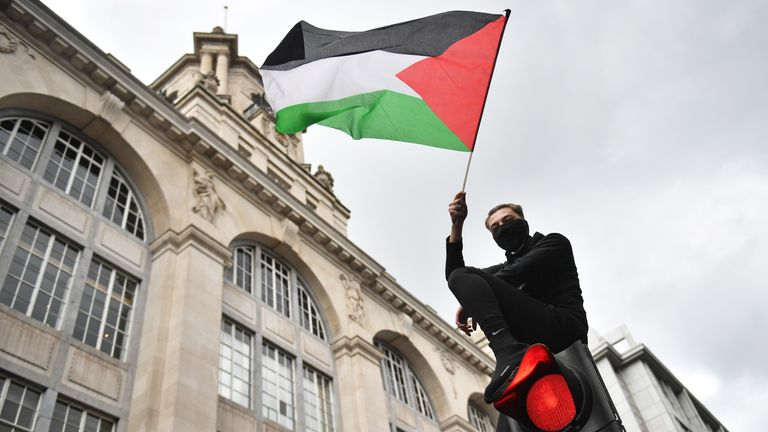 A demonstrator waves a Palestinian flag whilst sat atop a traffic light in London, during a march in solidarity with the people of Palestine amid the ongoing conflict with Israel. Picture date: Saturday May 15, 2021.