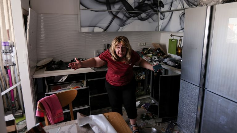 A woman reacts at her kitchen in an apartment of a damaged building following a rocket attack from Gaza, in Ashdod, Israel May 17, 2021. REUTERS/Ronen Zvulun