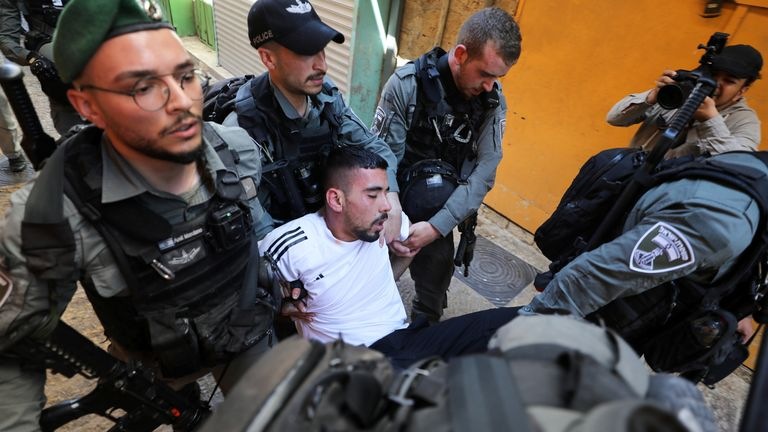 One protestor, who appears to be unconscious, is carried away by Israeli security force members