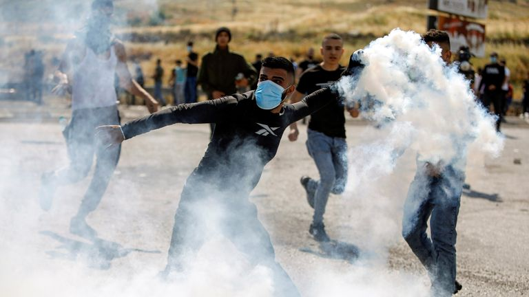 A Palestinian demonstrator hurls back a tear gas canister fired by Israeli forces during a protest over tension in Jerusalem and Israel-Gaza escalation, near Hawara checkpoint near Nablus in the Israeli-occupied West Bank, May 14, 2021. REUTERS/Raneen Sawafta