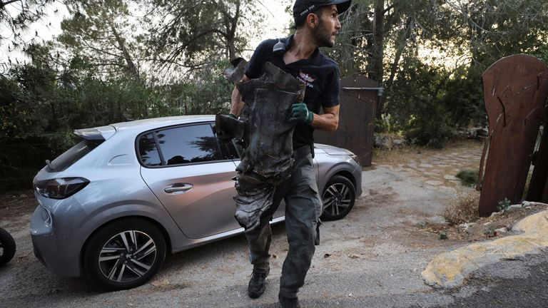 An Israeli forensics expert carries the remains of a rocket in the outskirts of Jerusalem