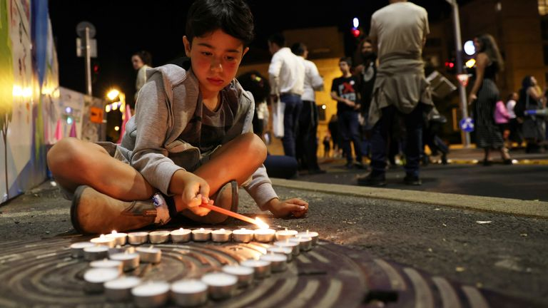 A boy lights candles during a vigil for the people killed and injured in a stampede at an ultra-Orthodox Jewish festival on the slopes of Israel's Mount Meron, in Jerusalem May 1, 2021. REUTERS/Ronen Zvulun