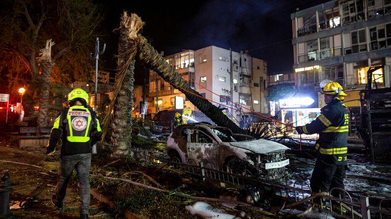 Firefighters work their way through wreckage in Holon, near Tel Aviv. Pic: AP