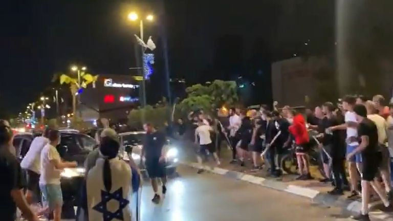 A crowd waving Israeli flags and carrying batons prepare to hit the passing car in Ramala. Pic: @bar_peleg