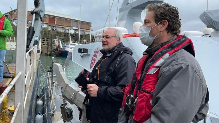 Jersey's assistant environment minister Gregory Guida (L) spoke to French fishermen from a boat