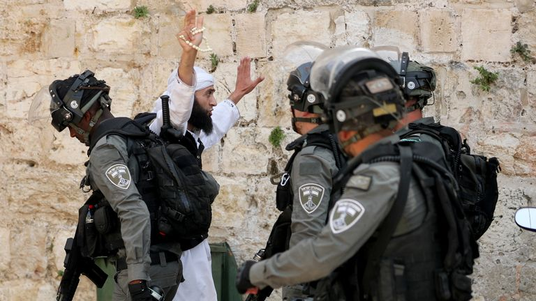 A Palestinian gestures as he confronts Israeli police