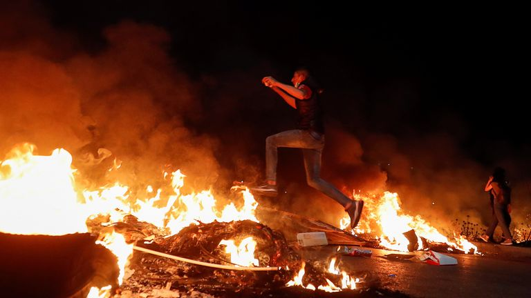 A Palestinian demonstrator jumps over a burning barricade during an anti-Israel protest over tension in Jerusalem, near the Jewish settlement of Beit El near Ramallah, in the Israeli-occupied West Bank May 9, 2021. REUTERS/Mohamad Torokman