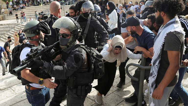 A Palestinian woman reacts during scuffles with Israeli security force members