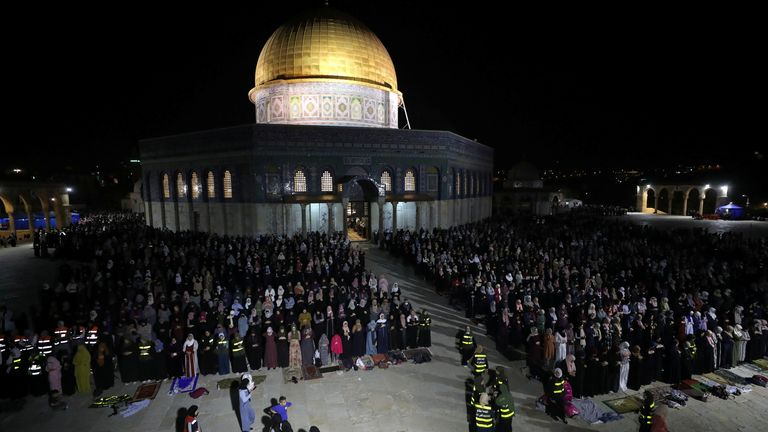 Palestinians pray in front of the Dome of the Rock in Jerusalem's Old City on Saturday night