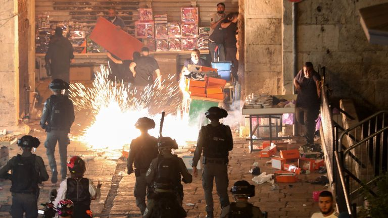 Palestinians react as Israeli police fire a stun grenade during clashes at Damascus Gate on Laylat al-Qadr during the holy month of Ramadan, in Jerusalem's Old City, May 9, 2021. REUTERS/Ronen Zvulun