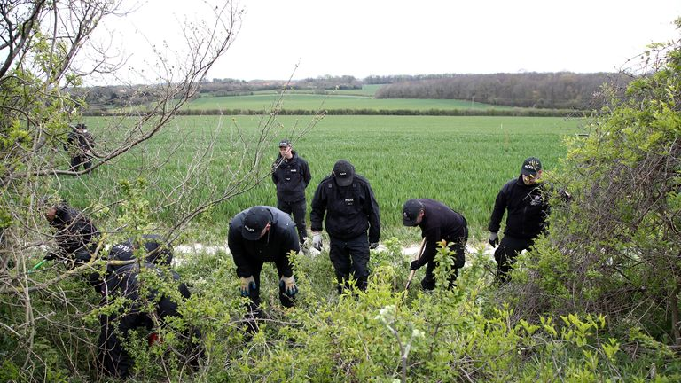 Police officers search fields near where PSCO Julia James was found dead