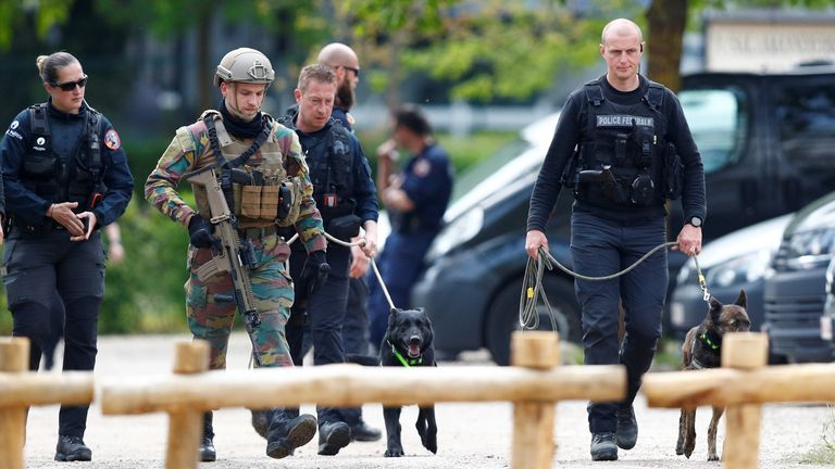 Police and army personnel with search dogs