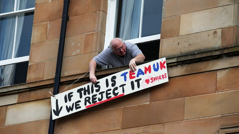 A man holds a protest sign on Kenmure Street