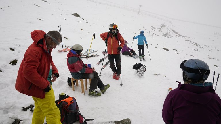 Skiers rest during heavy snowfall at the Lake District Ski Club