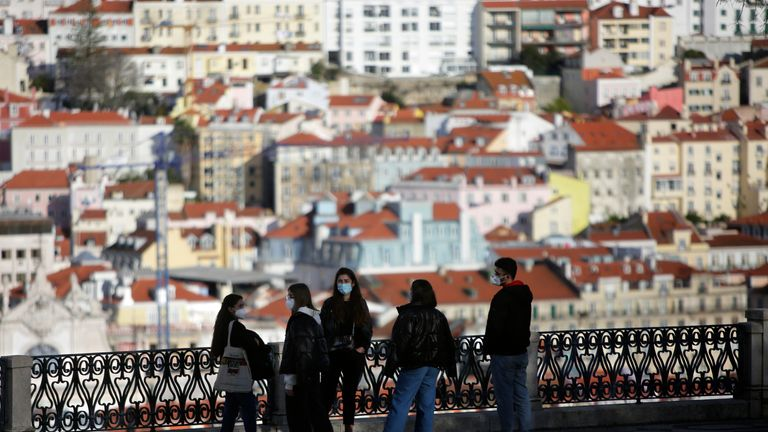 A group of young people wearing face masks chat at a viewpoint overlooking Lisbon's old centre. Pic: AP