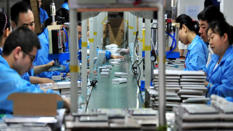 Employees work on a production line manufacturing lithium battery products at a factory in Yichang,