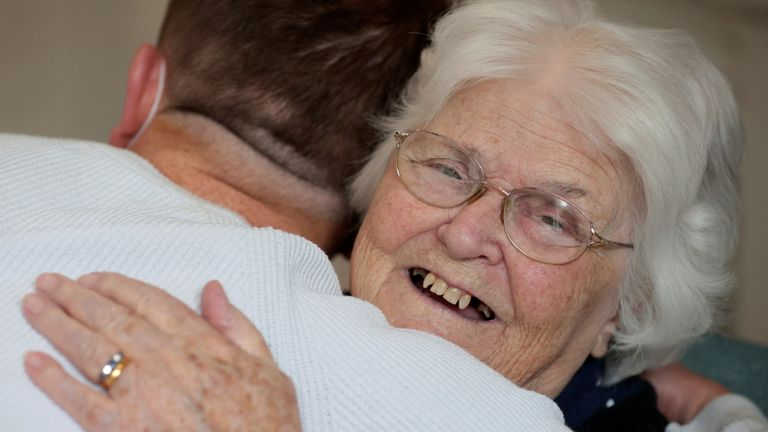 Terence Surin, a community coordinator, hugs care home resident Pam Harrison in Wimbledon