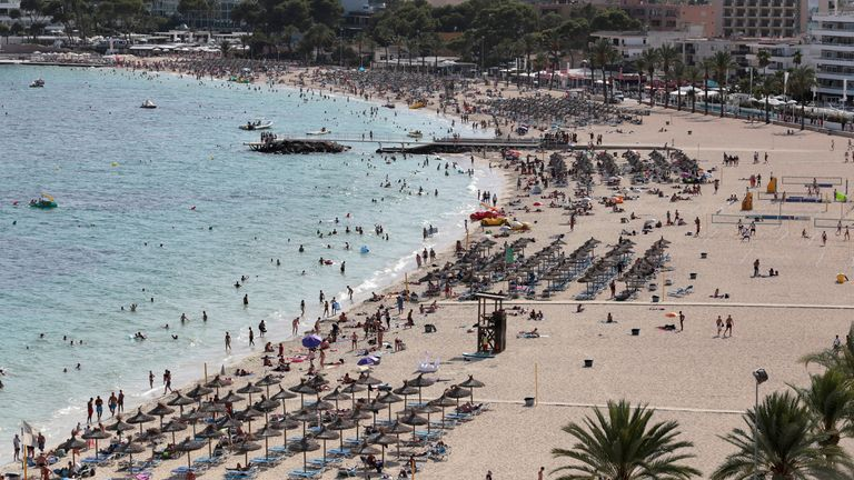 Tourists sunbathe and swim at the beach of Magaluf on the island of Mallorca, Spain, in 2017