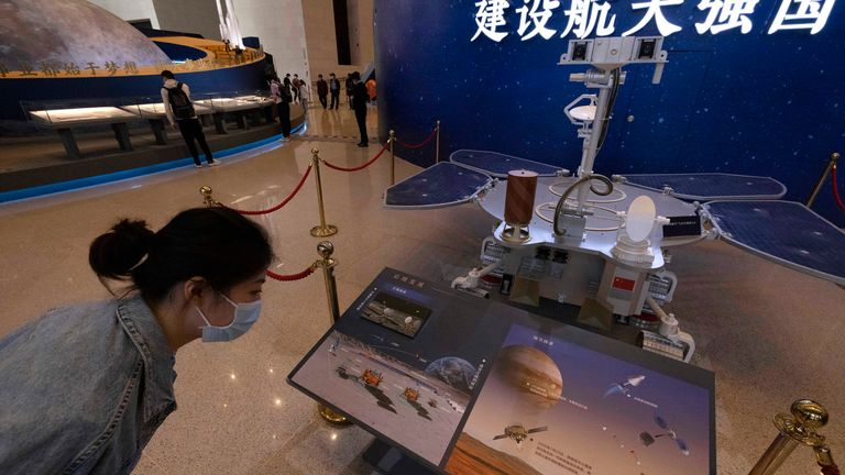 A visitor to an exhibition admires a replica of the Zhurong rover, which is about the size of a small car. Pic: AP
