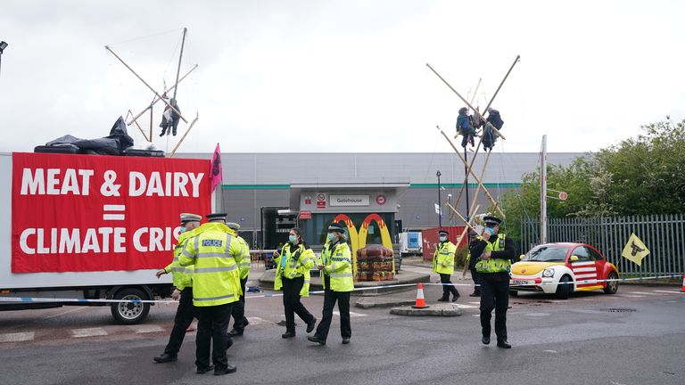 Animal Rebellion protesters suspended from a bamboo structure and on top of a van