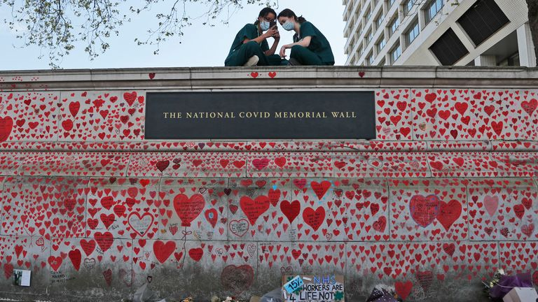 Nurses from the nearby St Thomas hospital have a rest on the National Covid Memorial Wall in London, Tuesday, April 27, 2021. British Prime Minister Boris Johnson has denied a press report which quoted him as allegedly saying he would rather see ...bodies pile high in their thousands... than impose a third national lockdown on the country. The Daily Mail claimed that Johnson made the comment in the fall of 2020, when his government imposed a second lockdown to combat a surge in coronavirus cases. (AP Photo/Frank Augstein)