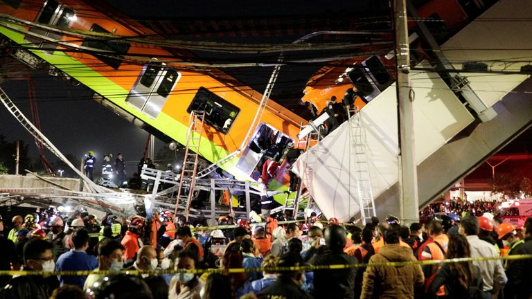 Rescuers work at a site where an overpass for a metro partially collapsed with train cars on it at Olivos station in Mexico City, Mexico May 3, 2021.