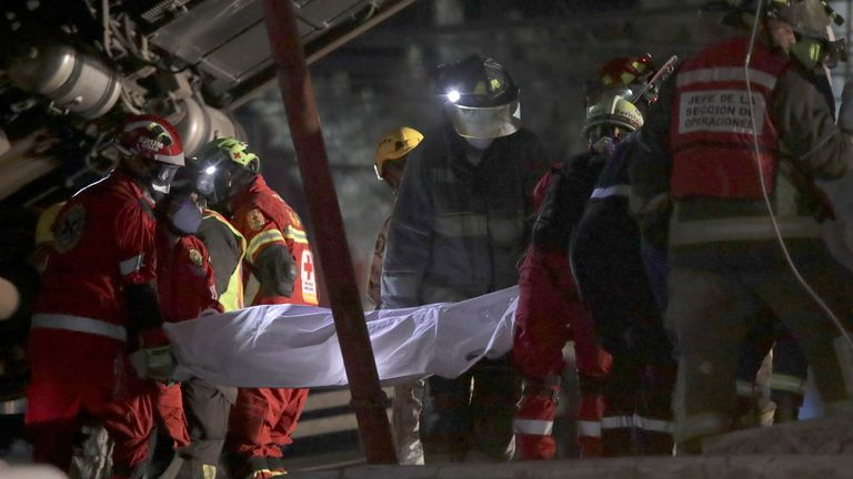 Rescuers retrieve a body from the accident site
