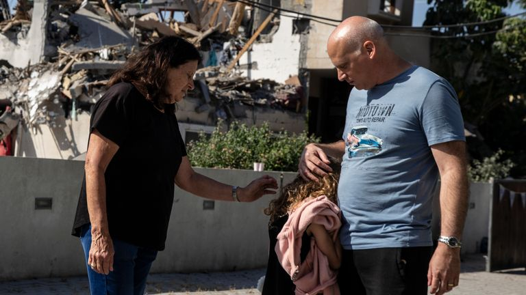 A young girl is comforted by her father next to a house damaged by a rocket fired from the Gaza Strip, in Yehod, central Israel. Pic: AP