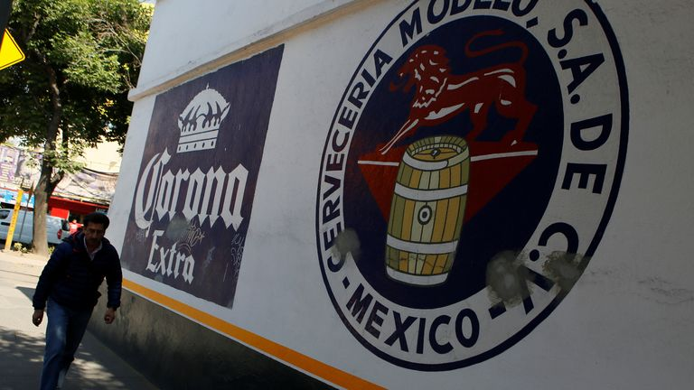 A man walks past the logo of Corona beer (L), produced by Group Modelo, in Mexico City, Mexico January 27, 2017