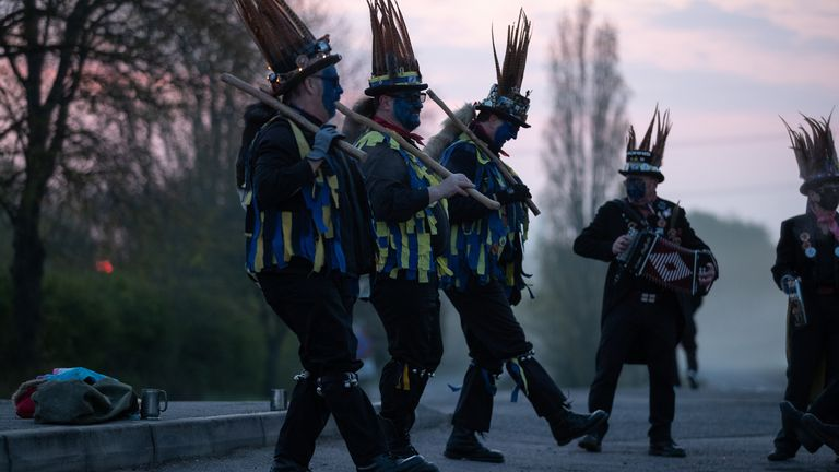 Members of the Hook Eagle Morris Men perform outside the Shack Cafe near to Hook in Hampshire as they see in the May Day dawn. It is the first time they have been able to perform together since January 2020 and is the first time they have performed in their new Blue face paint. Picture date: Saturday May 1, 2021.