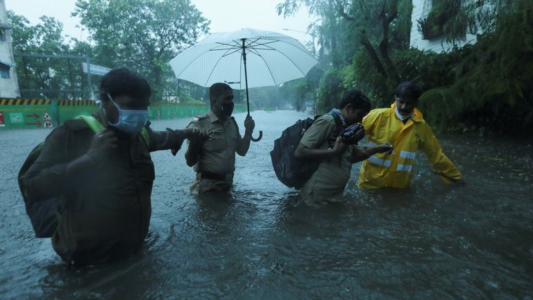 Frontline workers help people cross a flooded street after heavy rainfall caused by Cyclone Tauktae in Mumbai